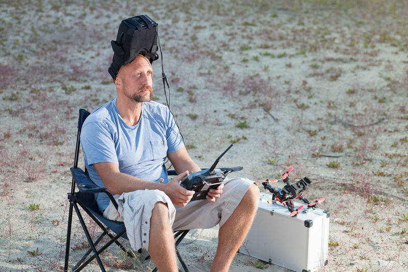 Man sitting with drone and remote control on field