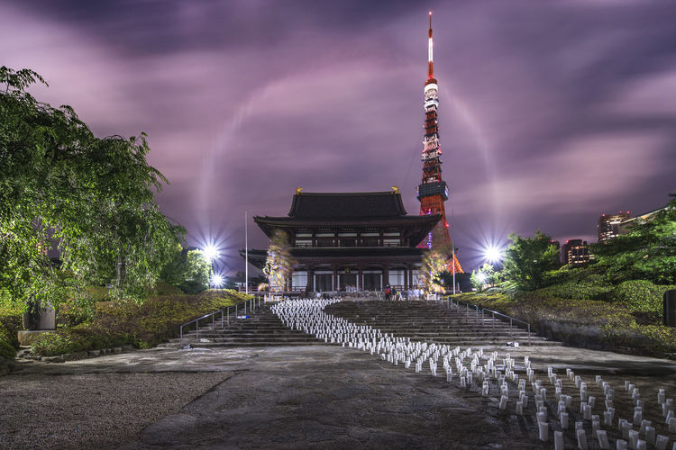 Illuminated temple amidst buildings against sky in city