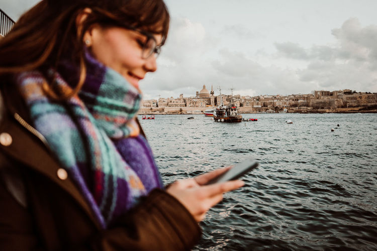 Smiling young woman using mobile phone by sea against sky