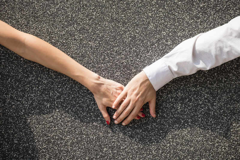 High angle view of couple hands