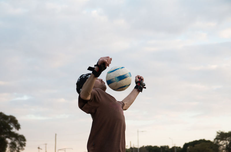 Low angle view of man playing soccer outdoors