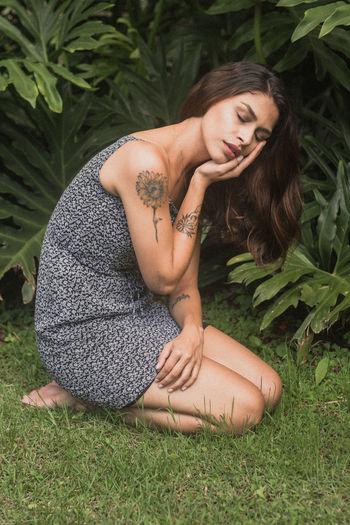 Full length of woman kneeling on grass