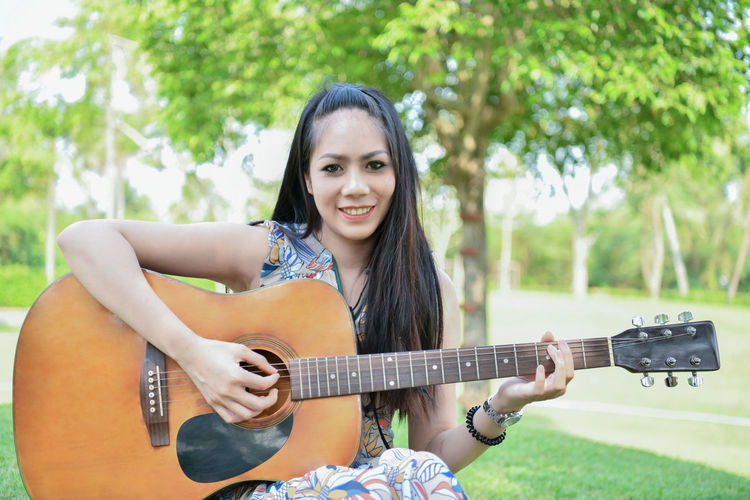 Portrait of smiling young woman playing guitar while sitting at park