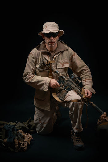 special forces soldier of the united states poses with a rifle on a black background Hat Soldier Warrior Adult Adults Only Assault Rifles Black Background Combat Day Full Length Holding Military One Man Only One Person Only Men Outdoors People Rifle Standing Studio Shot War Weapon