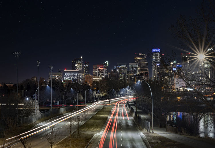Light trails on road amidst buildings against sky at night