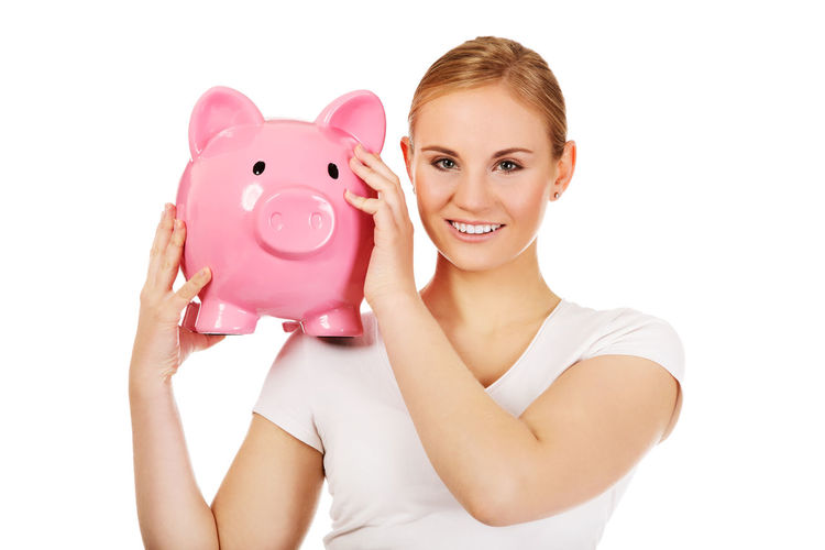 Portrait of smiling young woman holding piggy bank against white background