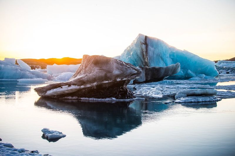 Icebergs In Sea Against Clear Sky During Sunset