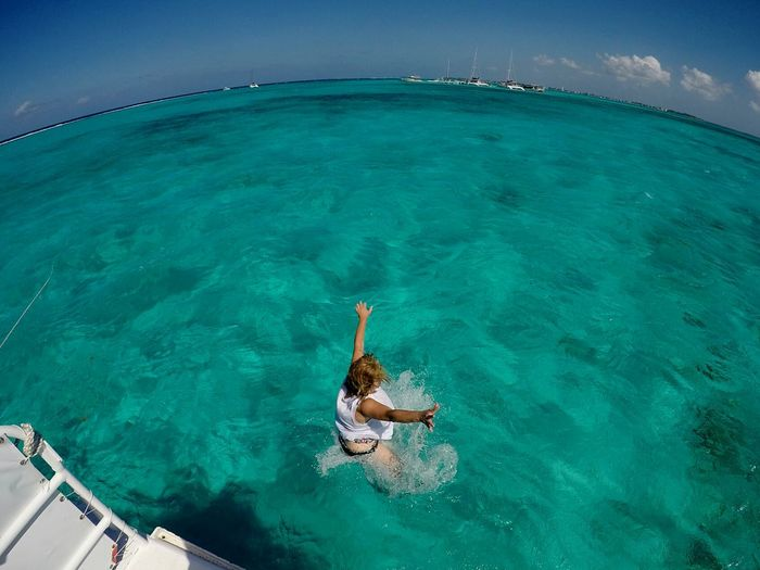 Fish-eye view of woman with arms outstretched jumping into sea