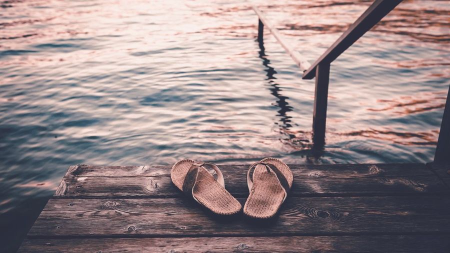 High Angle View Of Slippers On Pier At Lake