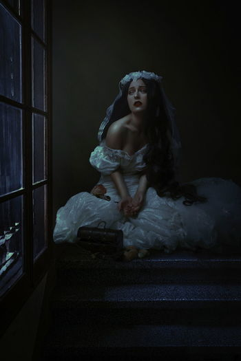 Young woman crying while sitting by window at night