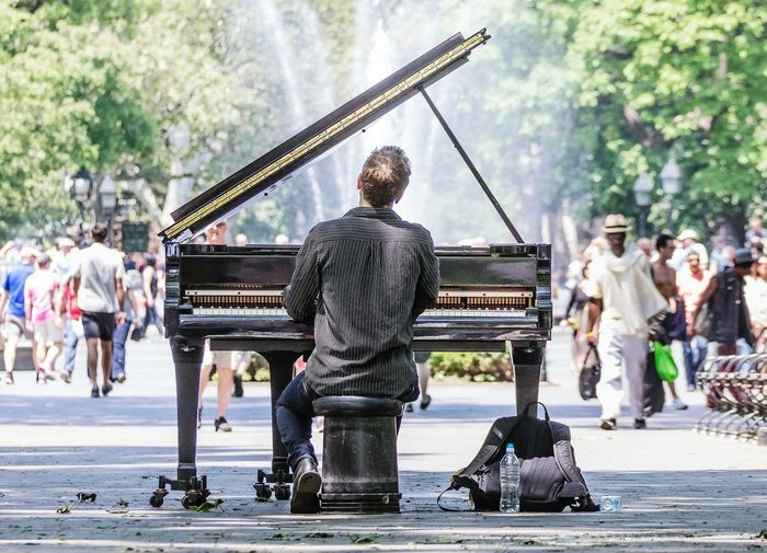 Man Playing Piano While Sitting On City Street