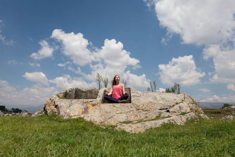 Low angle view of woman meditating while sitting on inca rock against sky