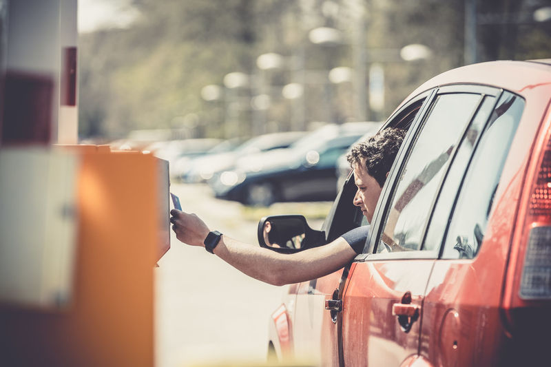 Man holding accessing credit on machine from car window