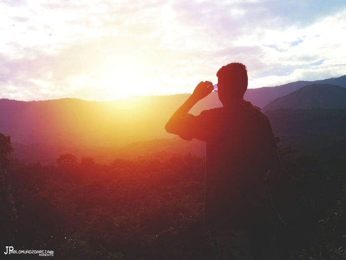 Beauty In Nature Camera - Photographic Equipment Day Landscape Leisure Activity Lifestyles Men Mountain Nature One Person Outdoors People Photographing Photography Themes Real People Rear View Scenics Silhouette Sky Standing Sunset Technology Wireless Technology