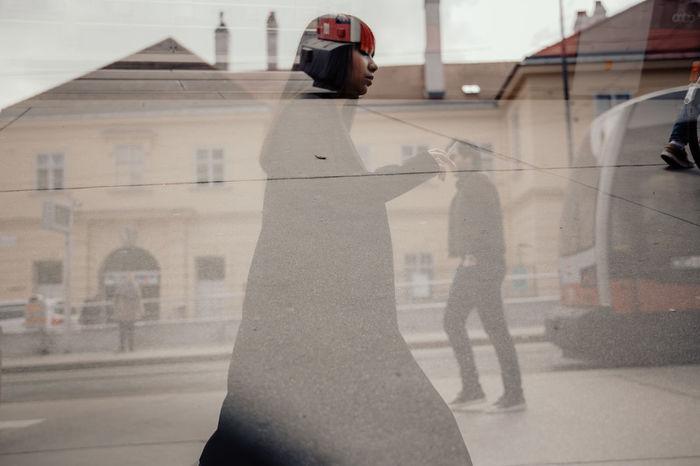 REFLECTION OF WOMAN WALKING IN CITY STREET