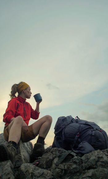 caucasian female hiker sitting on a rocky peak next to a backpack drinking beverage out of a mug Alpine Backpacking Boots Camping Expedition Freedom Hiking Nature Sitting Travel Trekking Woman Active Activity Adventure Backpack Communication Copy Space Female Hobby Holding Leisure Activity Lifestyles Men Mountain Nature One Person Outdoors Peak People person Photographing Photography Themes Real People Rock Rock - Object Sitting Sky Solid Technology Trek Wireless Technology
