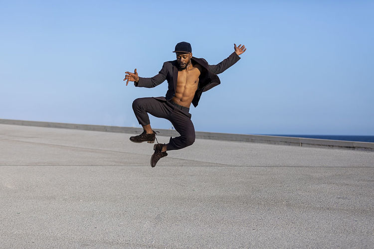 Front view young black man wearing casual clothes jumping in urban background. Lifestyle concept. Millennial african guy wearing sunglasses outdoor Full Length One Person Real People Jumping Mid-air Leisure Activity Lifestyles Sky Casual Clothing Men Nature Land Young Men Day Young Adult Clear Sky Sunlight Human Arm Enjoyment Outdoors Arms Raised African American Black Man Dancing Muscular Build Suit Daylight Blue Sky Copy Space Males  Man Bearded Elegant Attractive Wellbeing