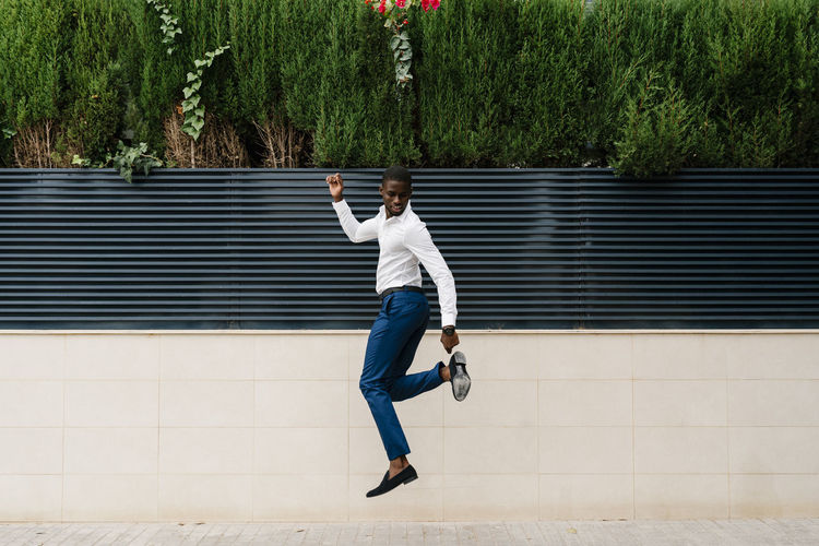 Full length rear view of man jumping