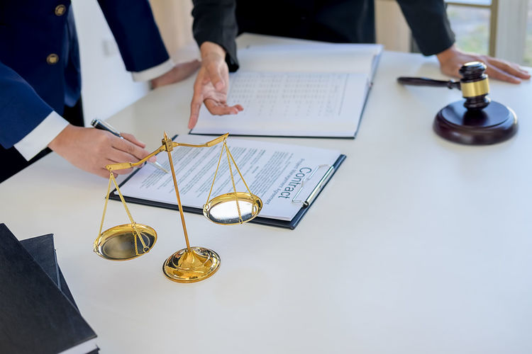 Midsection of lawyer guiding businessman during contract form filling on desk