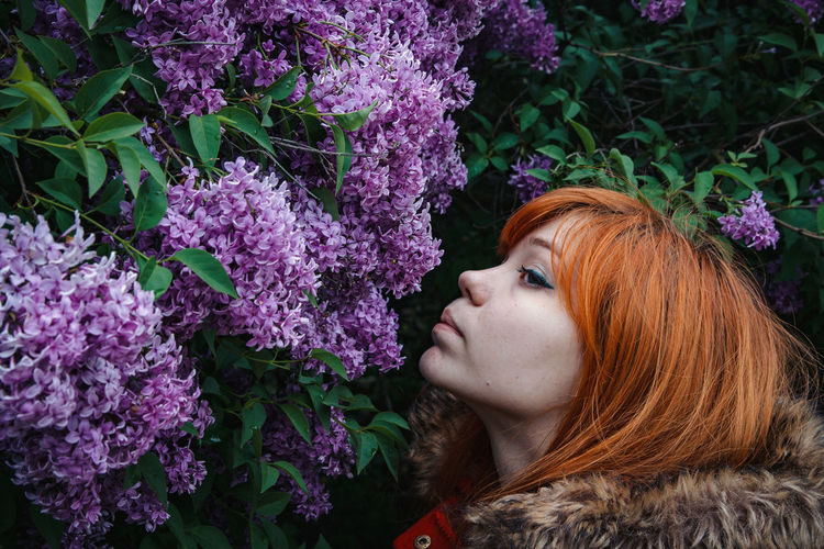 Close-up of woman smelling lilac flowers