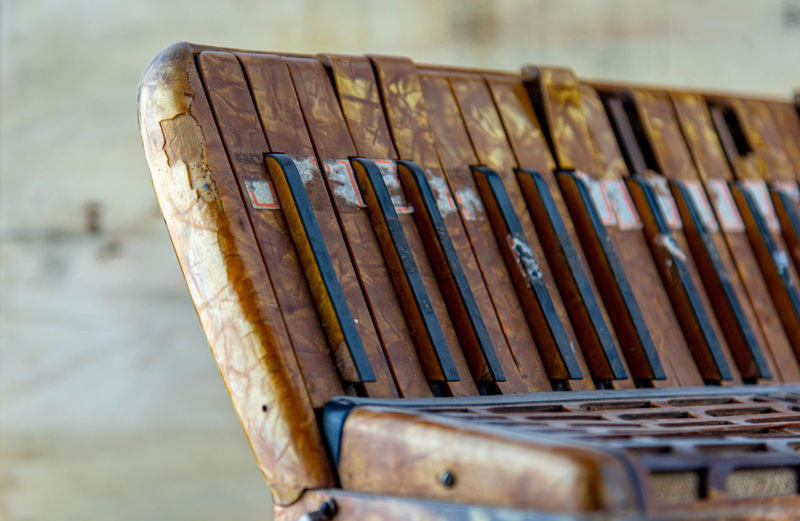 Close-up of old bench in row