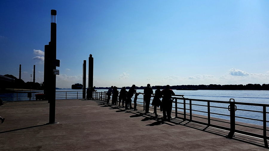 Silhouette people standing on pier by sea against clear sky