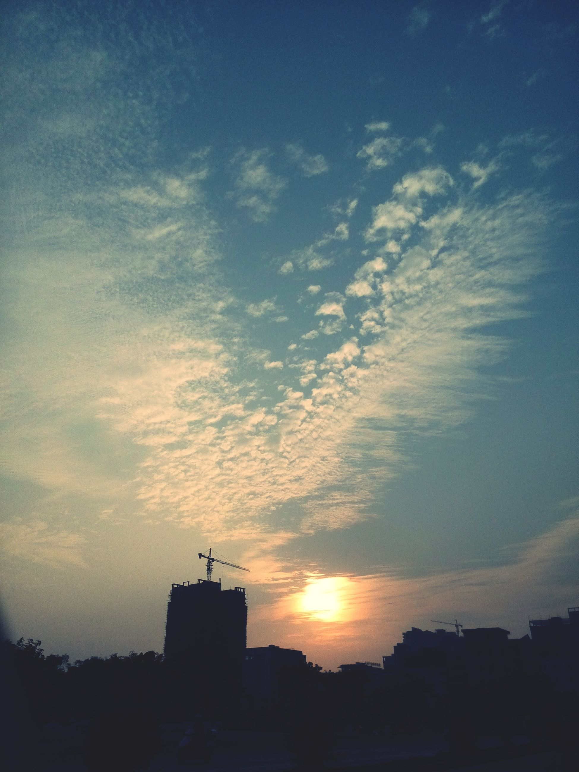 sunset, silhouette, building exterior, sky, architecture, built structure, sun, cloud - sky, sunlight, beauty in nature, scenics, orange color, cloud, nature, house, sunbeam, tranquil scene, outdoors, low angle view, tranquility