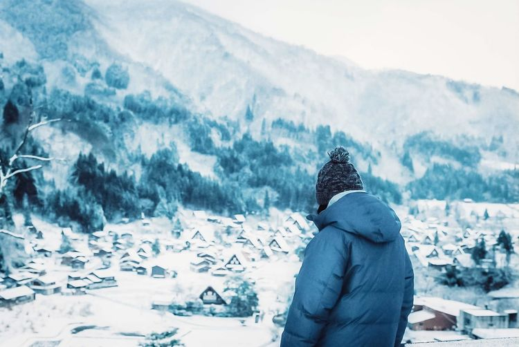 Rear view of person standing on snow covered mountain