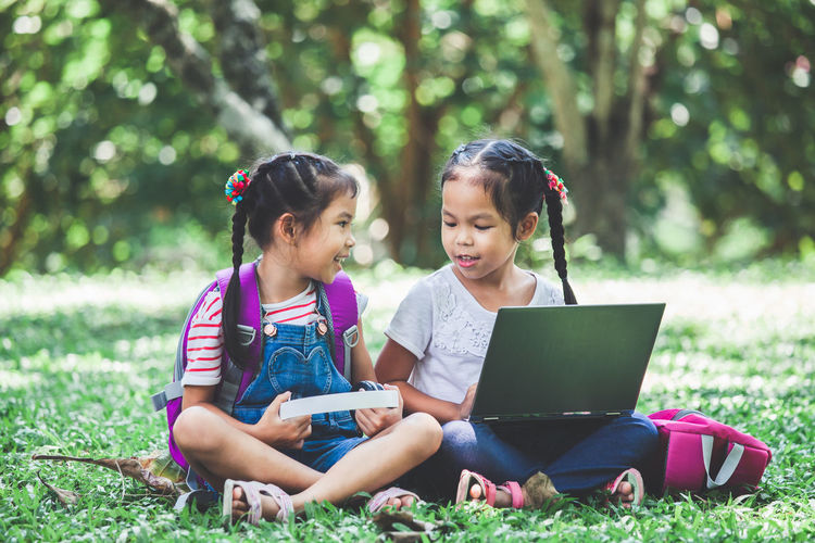 Schoolgirls Talking While Using Laptop While Sitting In Park