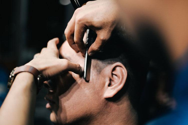 Barber cutting hair of customer at salon