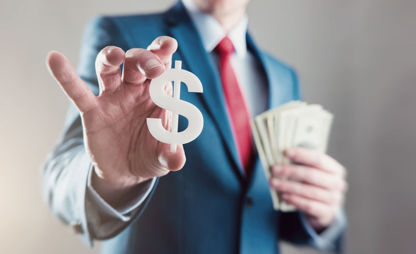 Midsection Of Businessman Holding Dollar Sign And Paper Currencies While Standing Against Gray Background