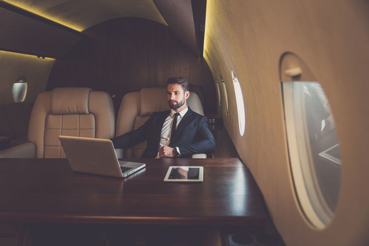Businessman with laptop on table sitting on airplane