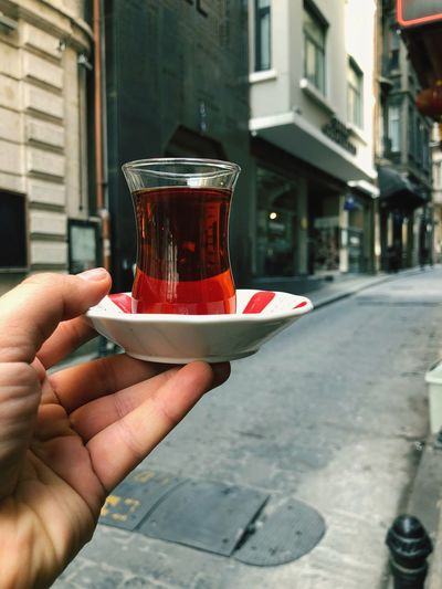 Traditional Drink Turkish Tea Culture Turkish Teacup Turkish Tea Tea Human Hand Hand Drink Holding Food And Drink Human Body Part Refreshment Real People Lifestyles Focus On Foreground One Person Architecture Unrecognizable Person Personal Perspective Building Exterior Built Structure City Body Part Focus On The Story The Traveler - 2018 EyeEm Awards The Street Photographer - 2018 EyeEm Awards #urbanana: The Urban Playground