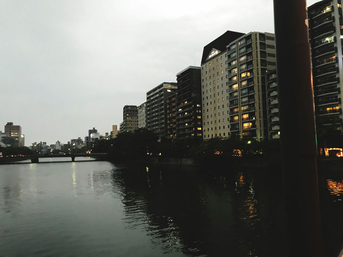River by illuminated buildings against sky at dusk