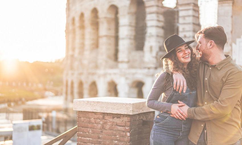 Romantic young couple standing against coliseum