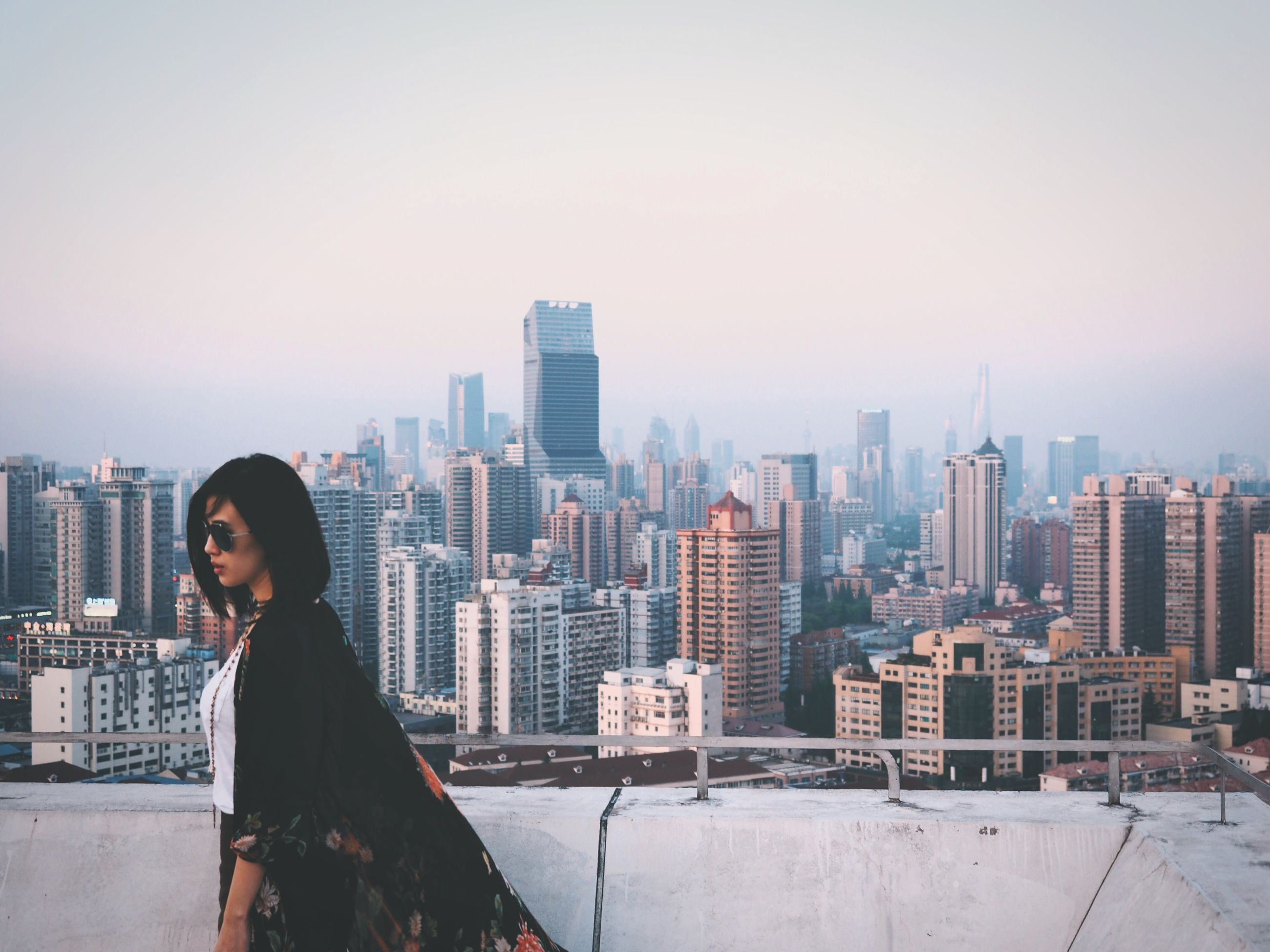 building exterior, city, architecture, built structure, cityscape, lifestyles, skyscraper, leisure activity, standing, clear sky, young adult, casual clothing, city life, looking at view, tower, tall - high, sky, waist up