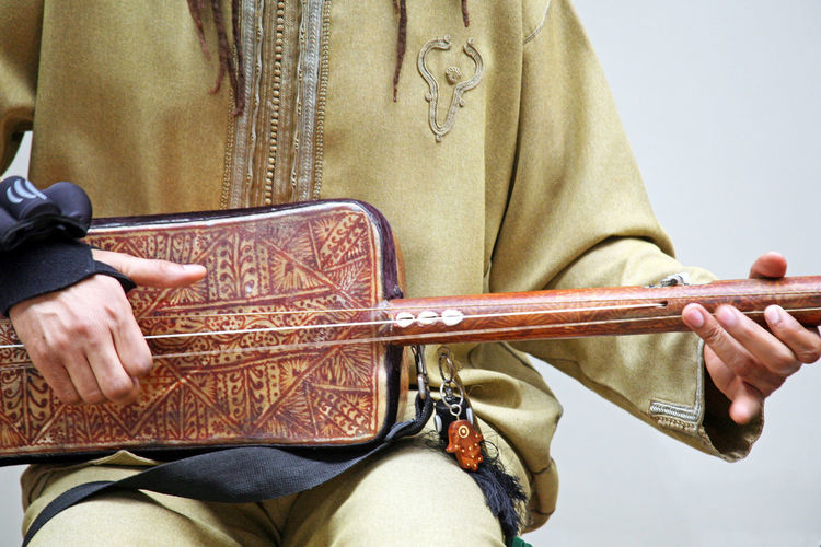 Midsection of man playing string instrument against wall