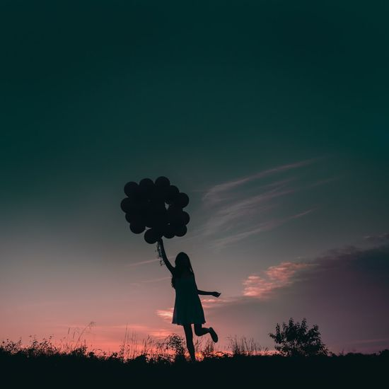 Silhouette Of Young Girl Holding Balloons