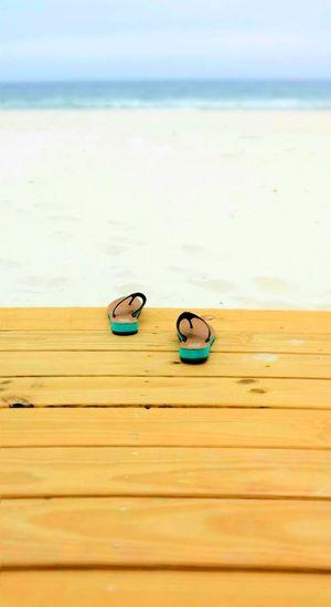Flip-flops on boardwalk at beach against sky