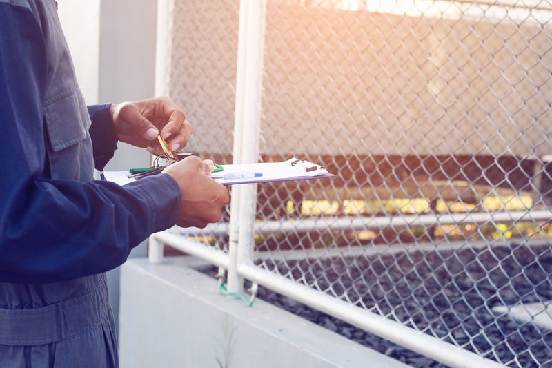 Midsection of worker holding clipboard by chainlink fence