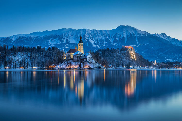 Bled castle in lake by mountains at dusk