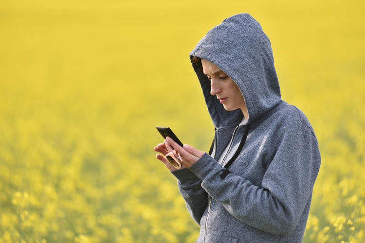 Woman Using Phone While Standing On Field