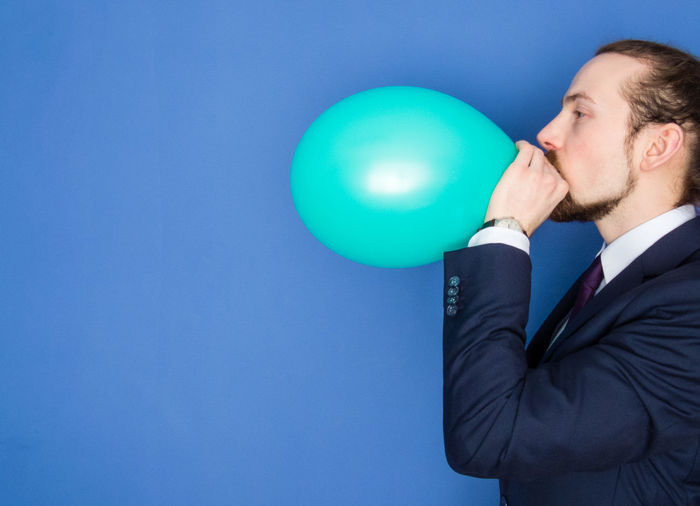 Side view of businessman blowing green balloon against blue background