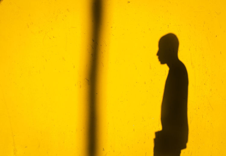 Silhouette of person standing against yellow wall