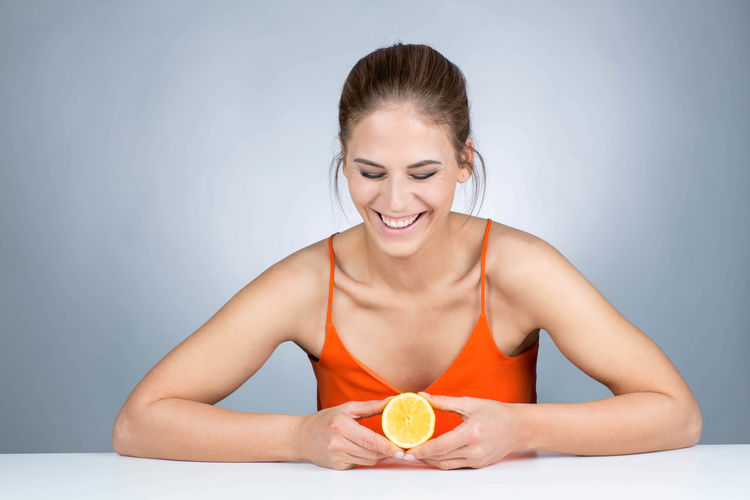 beautiful young woman holds a lemon and laughs Laughing Woman Beautiful Woman Beauty Beauty In Nature Food Front View Gray Background Healthy Healthy Eating Healthy Lifestyle Helathylifestyle Holding Indoors  Lemon One Person Smiling Smling Sour Sour Taste Studio Shot Vitamin Vitamin C Women Young Women