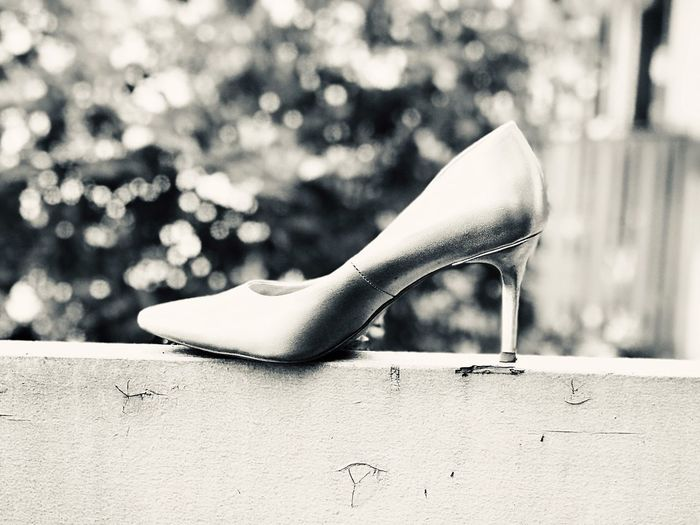 Close-up of high heels on retaining wall outdoors