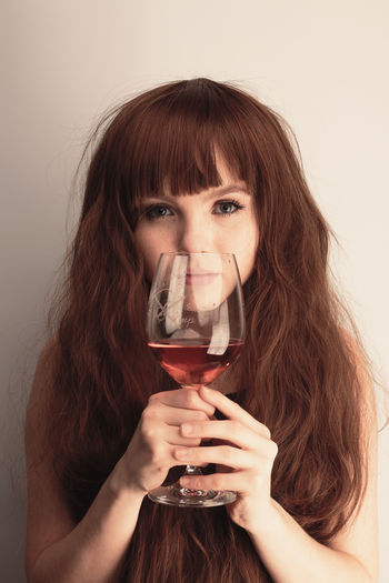 Portrait Of Young Woman Holding Wineglass Against White Background