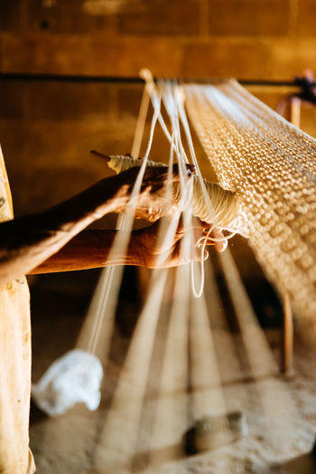 Midsection of woman waving wool in loom