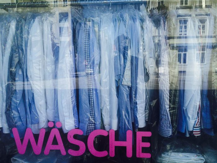 Shirts hanging at store seen through glass