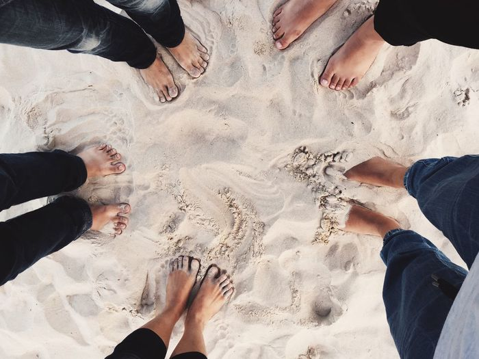 Low section of friends standing on sand at beach